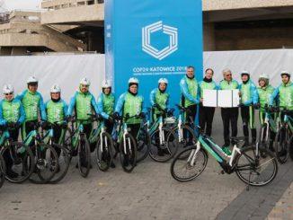 Des cyclistes en vélos électriques font la promotion du transport à faible émission de carbone à la COP24